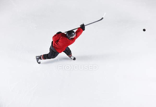 Jogador de hóquei em disco de tiro uniforme vermelho no gelo — Fotografia de Stock