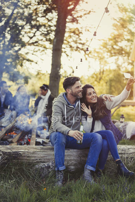 Couple posing for selfie with camera phone near campfire — Stock Photo