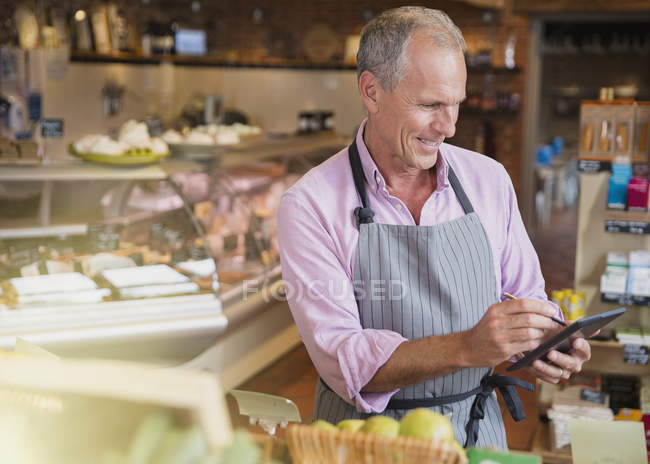 Smiling grocery worker checking inventory with digital tablet and stylus in market — Stock Photo