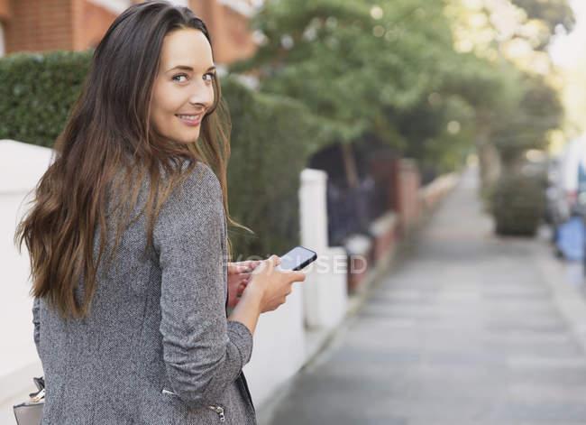 Ritratto donna d'affari sorridente con cellulare guardando indietro sul marciapiede — Foto stock