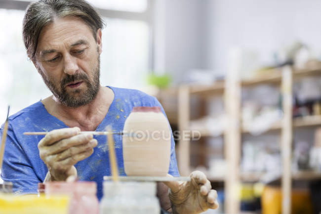 Focused mature man painting pottery vase in studio — Stock Photo