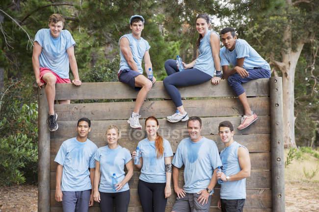 Retrato del equipo de confianza en la pared en la carrera de obstáculos del campamento de arranque - foto de stock