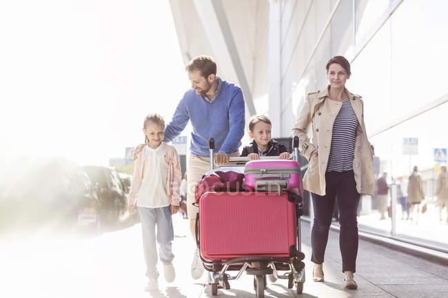 Famille avec chariot à bagages marchant en dehors de l'aéroport — Photo de stock