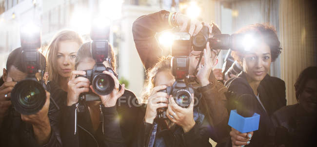 Portrait of paparazzi in a row with cameras and microphone — Stock Photo