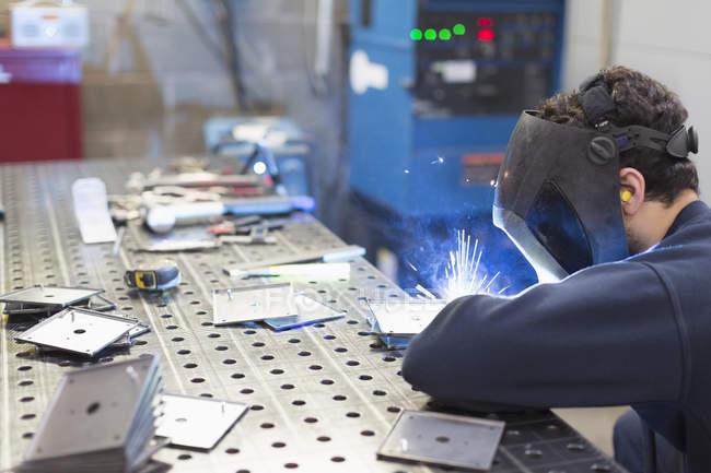 Welder welding pieces in steel factory — Stock Photo