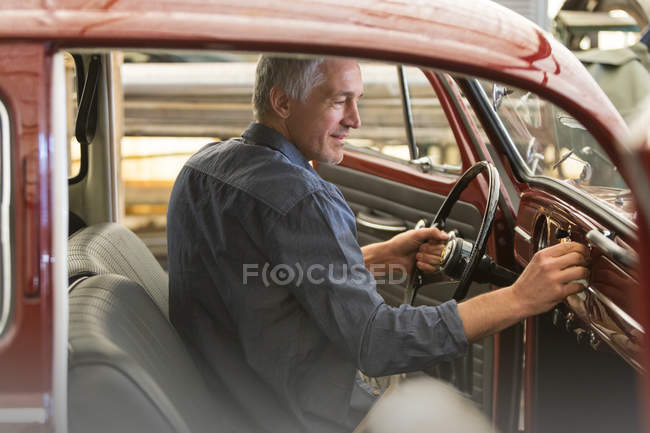 Mechanic inside classic car in auto repair shop — Stock Photo