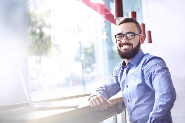 Ritratto di uomo d'affari sorridente con barba al computer portatile nel caffè — Foto stock