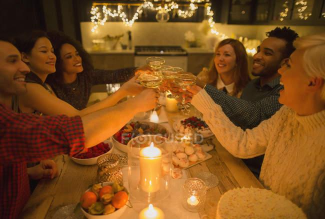 Друзья пьют бокалы шампанского за столом при свечах — стоковое фото