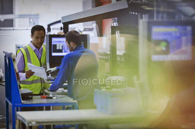 Supervisor and worker discussing paperwork at machine in steel factory — Stock Photo