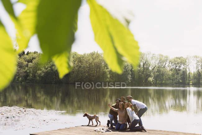 Quai des amis avec caméraphone prenant selfie ensoleillé au bord du lac — Photo de stock