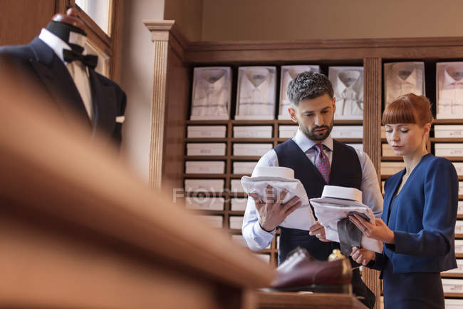 Работник показаны бизнесмен рубашки в магазин мужской одежды — стоковое фото