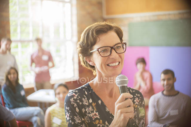Audiência atrás sorridente alto-falante com microfone no centro comunitário — Fotografia de Stock
