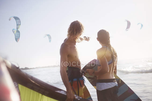 Couple watching kiteboarders over sunny ocean — Stock Photo