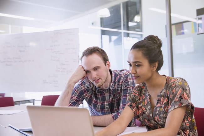 Studenti universitari che studiano al computer portatile in aula — Foto stock