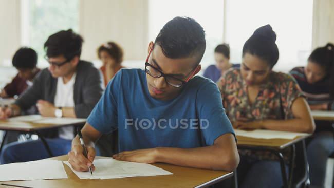 Studente di college maschile che fa test alla scrivania in classe — Foto stock