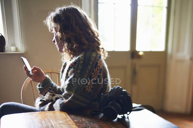 Девушка переписывается с телефоном, щенок спит на коленях. — стоковое фото