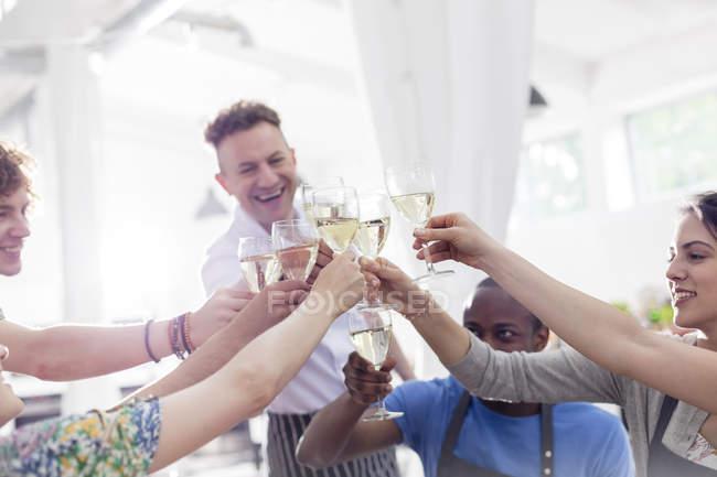 Professora de chef e alunos brindam copos de vinho na cozinha da aula de culinária — Fotografia de Stock