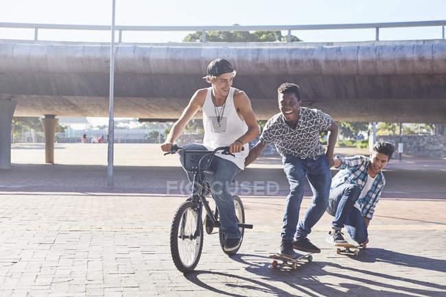 Teenage boys riding BMX bicycle and skateboarding at sunny skate park — Stock Photo