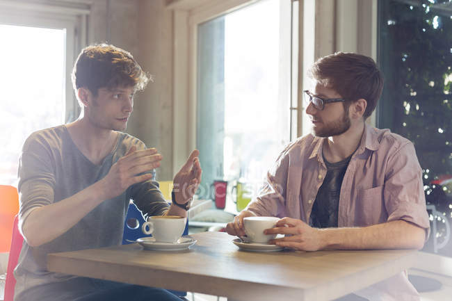 Men talking and drinking coffee in cafe — Stock Photo