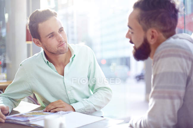 Creative businessmen meeting in modern cafe — Stock Photo