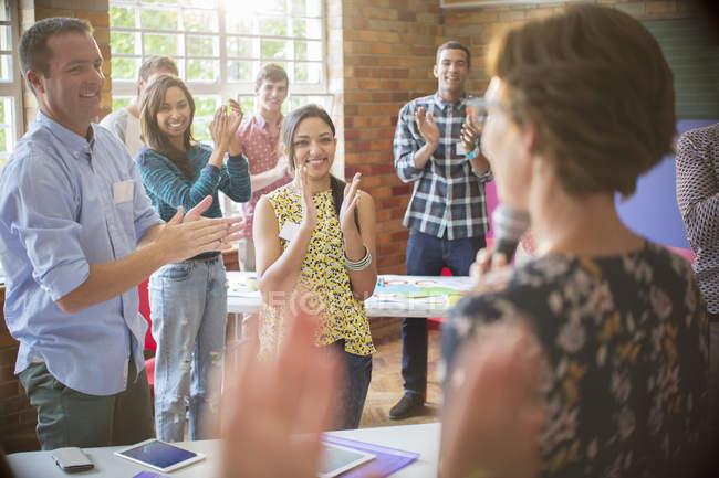 Plateia batendo palmas para alto-falante dentro de casa — Fotografia de Stock