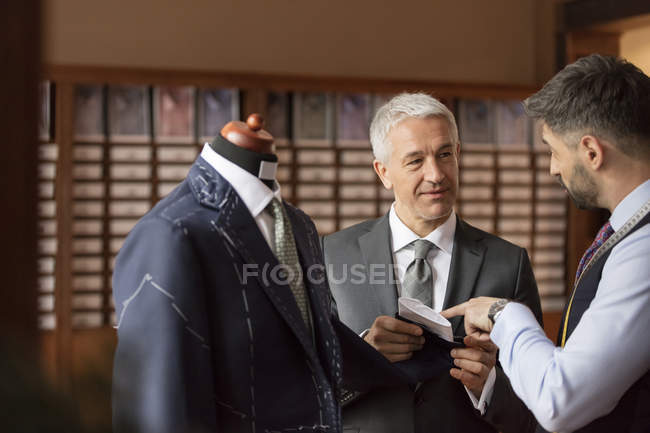Tailor explaining suit to businessman in menswear shop — Stock Photo