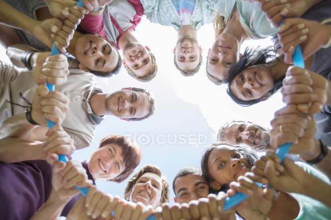 Portrait of team connected in circle around plastic hoop — Stock Photo