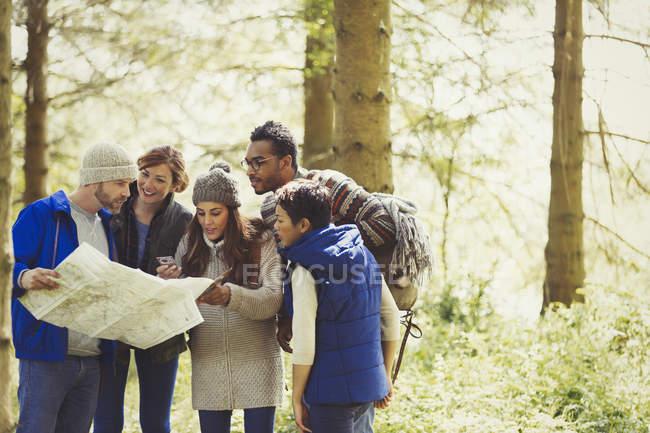 Amis avec carte randonnée dans les bois — Photo de stock
