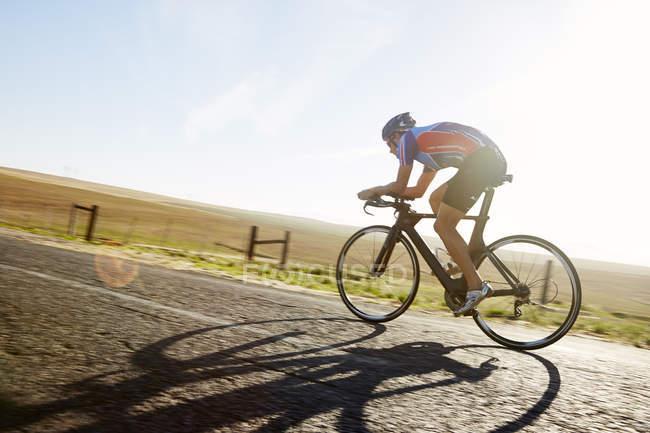 Cycliste triathlète homme cycliste sur route rurale ensoleillée au lever du soleil — Photo de stock
