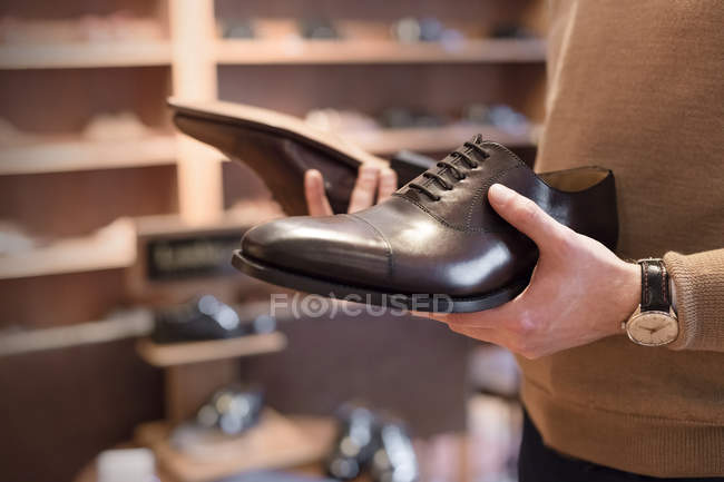 Businessman browsing dress shoes in menswear shop — Stock Photo