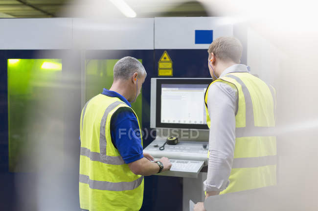 Workers at machinery control panel in steel factory — Stock Photo