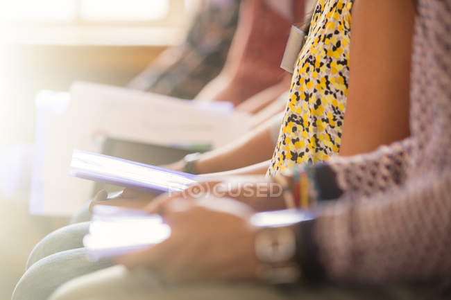 Midsection view of audience sitting in a row with paperwork — Stock Photo