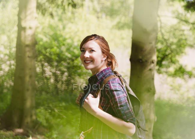 Donna sorridente con lo zaino trekking nel bosco pieno di sole — Foto stock