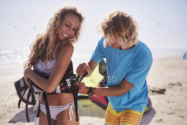 Harnais de sécurité kiteboarding homme fixation sur femme sur plage ensoleillée — Photo de stock