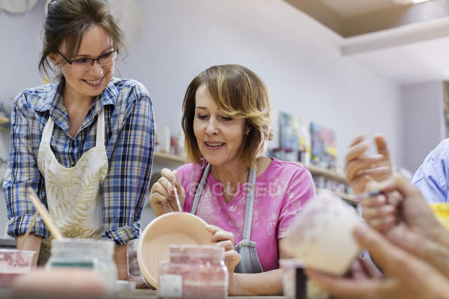 Mature woman painting pottery in studio — Stock Photo
