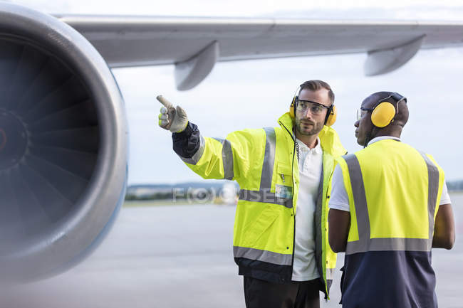 Air traffic control ground crew workers talking near airplane on airport tarmac — Stock Photo
