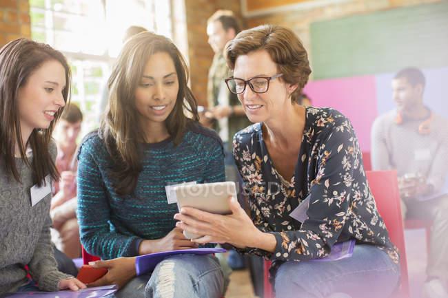 Tablette numérique de femme montrant aux femmes au centre communautaire — Photo de stock