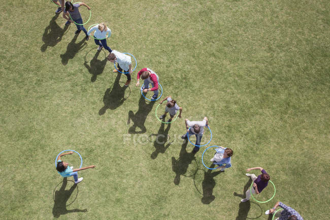 People spinning in plastic hoops in sunny field — Stock Photo