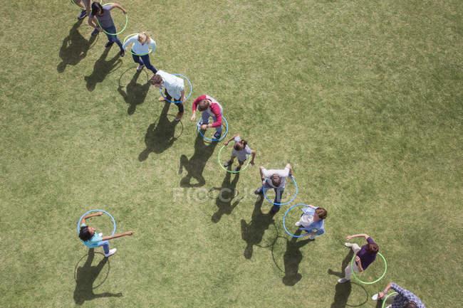 Les gens filant dans des cerceaux en plastique dans un champ ensoleillé — Photo de stock