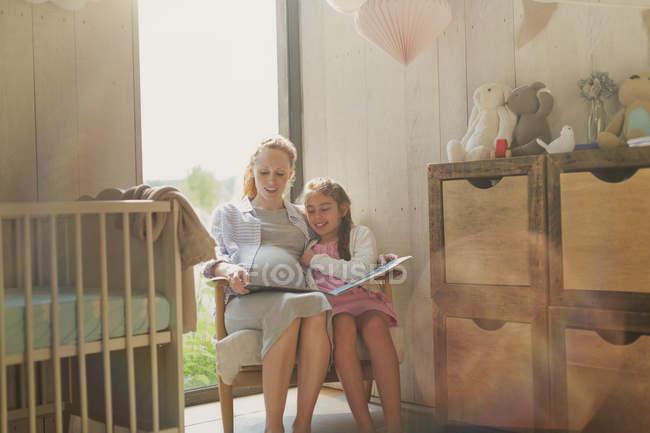 Madre e figlia incinte che leggono il libro di storia nella scuola materna — Foto stock