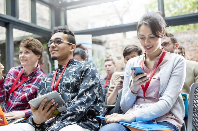 Texto femme avec téléphone cellulaire en public à la Conférence sur la technologie — Photo de stock