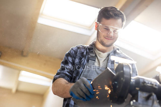 Smiling metal worker using sander in workshop — Stock Photo