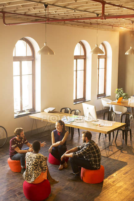 Creative business people talking in circle in office — Stock Photo