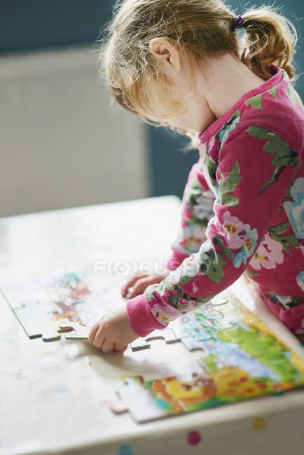 Маленькая девочка монтаж головоломки — стоковое фото