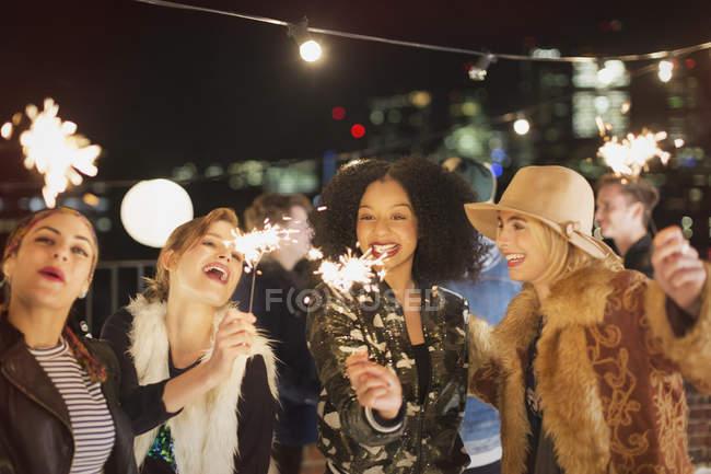 Giovani donne con scintille alla festa sul tetto — Foto stock