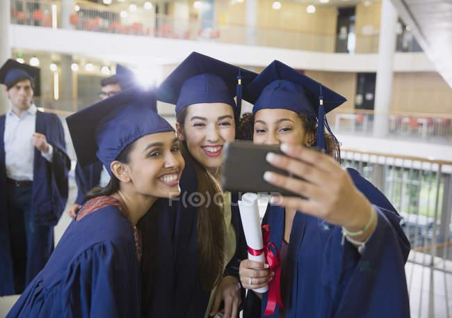 Diplômés du collégial féminin en bonnet et robe prenant selfie — Photo de stock