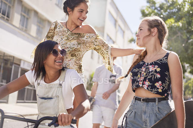 Teenage girls with BMX bicycle and skateboard on sunny urban street — Stock Photo