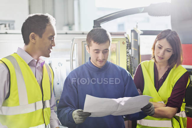 Workers reviewing paperwork in steel factory — Stock Photo