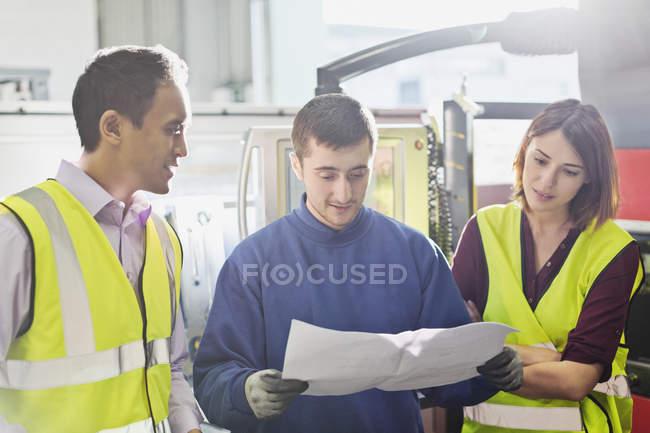 Trabalhadores que analisam papelada em fábrica de aço — Fotografia de Stock