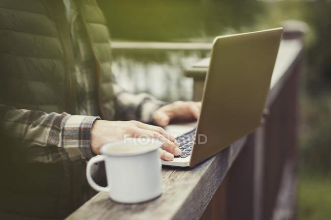 Mann benutzte Laptop und trank Kaffee an Balkongeländer — Stockfoto